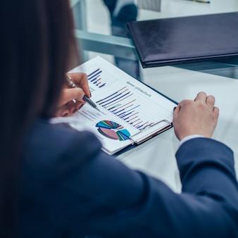Primo piano del team aziendale che discute i grafici finanziari su un posto di lavoro in un ufficio moderno