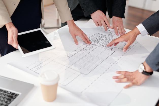 Primo piano del team aziendale per discutere piani e bozze durante la riunione in ufficio, copia dello spazio