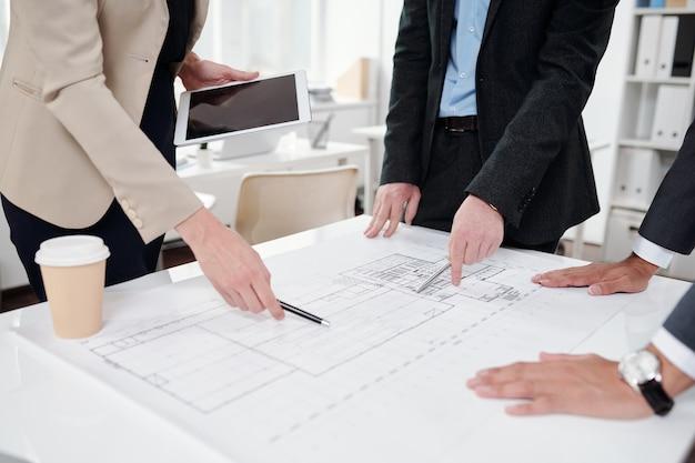 Primo piano del team aziendale che punta a piani e bozze mentre si discute del progetto di ingegneria durante la riunione in ufficio, copia dello spazio