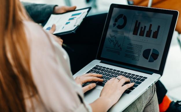 Primo piano del team aziendale che lavora al computer portatile con programmi finanziari sul posto di lavoro.