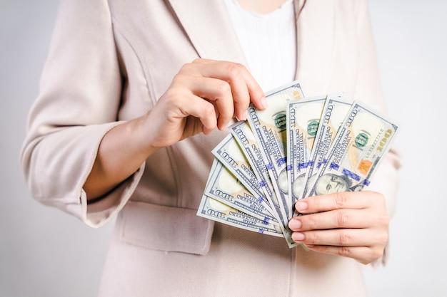 Primo piano delle mani della donna di affari che contano le banconote in dollari americani dei soldi su bianco. concetto di denaro.