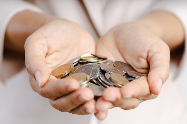 Il primo piano della donna di affari passa le monete della tenuta su bianco. concetto di risparmio di denaro.