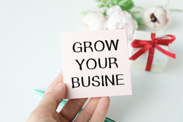 Primo piano sulla donna d'affari che tiene una carta con il testo grow your business, immagine del concetto di business con sfondo soft focus
