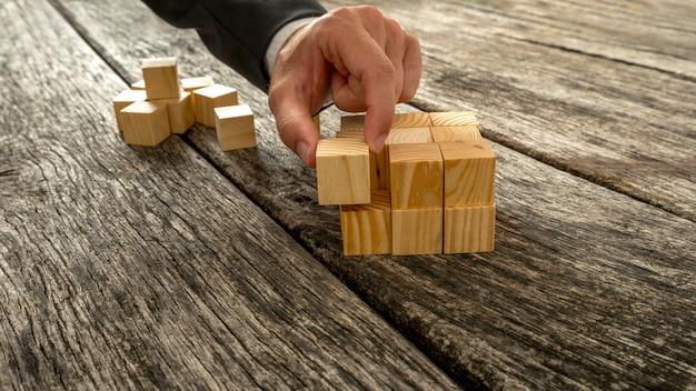 Primo piano dell'uomo d'affari che monta i cubi di legno in bianco in un intero strutturato