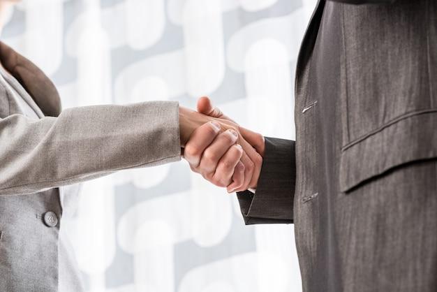 Primo piano dell'uomo d'affari e della donna d'affari che si stringono la mano in accordo