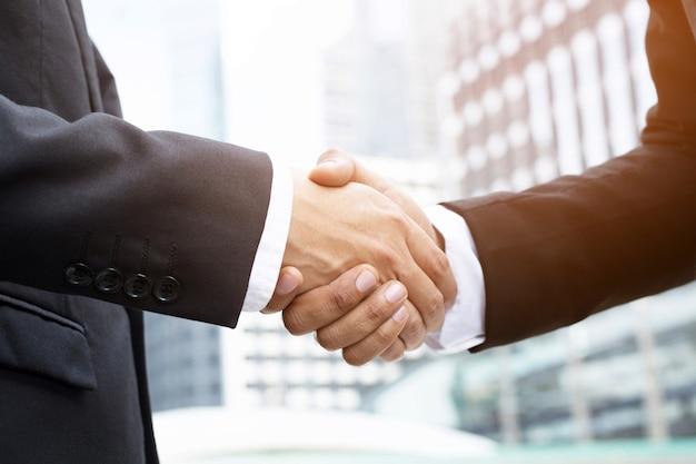 Primo piano di un investitore della stretta di mano dell'uomo d'affari tra due colleghi