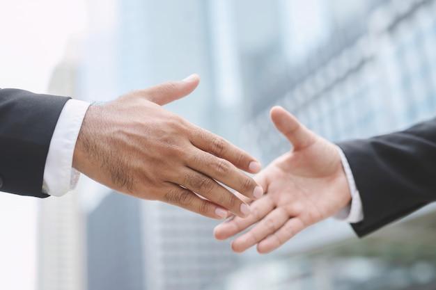 Primo piano di un investitore di scossa della mano dell'uomo d'affari fra due colleghi.