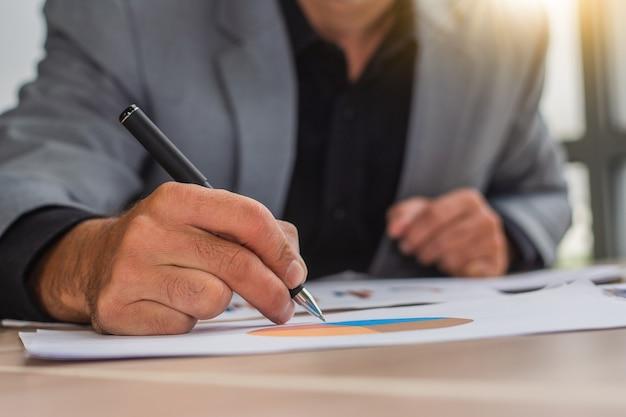 Scrittura della mano dell'uomo d'affari del primo piano con la penna