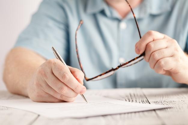Il primo piano delle mani dell'uomo d'affari che scrive qualcosa su pezzo di carta e che tiene gli occhiali