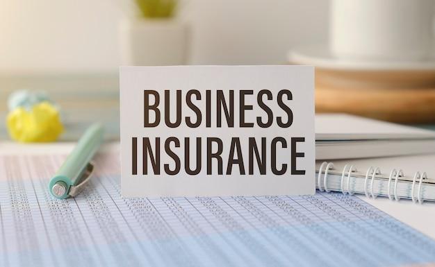 Primo piano sull'uomo d'affari che tiene una carta con testo business insurance, immagine del concetto di business con sfondo soft focus