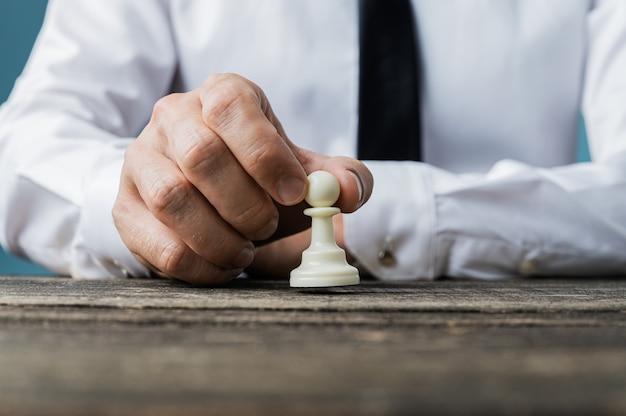 Primo piano dell'uomo d'affari mettendo pezzo degli scacchi pedone bianco sullo scrittorio di legno rustico in un'immagine concettuale.