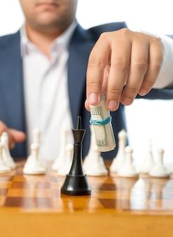 Uomo d'affari del primo piano che gioca con i dollari contorti al gioco di scacchi che