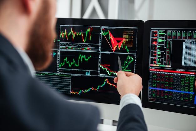 Primo piano dell'uomo d'affari che punta sul monitor del computer con grafici e grafici in ufficio