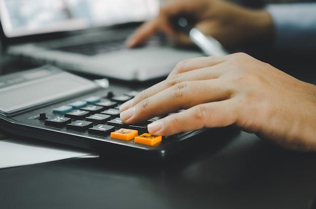 Primo piano della mano di un uomo d'affari e di una calcolatrice. affari, finanza, investimenti, fiscalità e economia concettuale