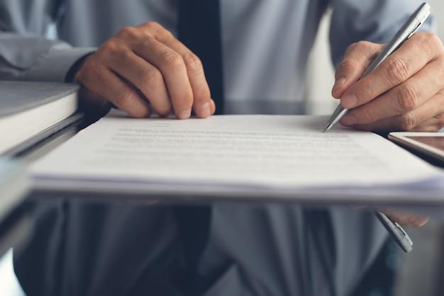 Primo piano dell'uomo d'affari che firma un contratto commerciale sul tavolo di vetro