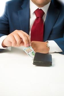 Uomo d'affari del primo piano che ruba soldi dal portafoglio