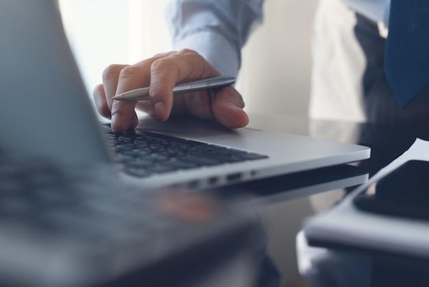 Primo piano dell'uomo d'affari che digita sul computer portatile in ufficio