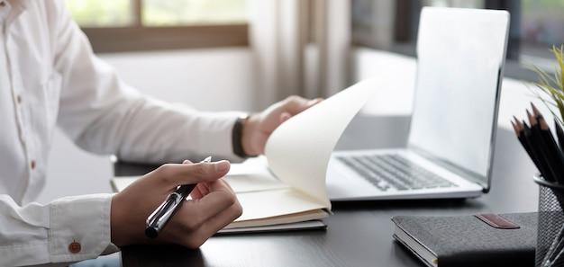 Uomo d'affari del primo piano che scrive sul taccuino su un tavolo con un computer portatile