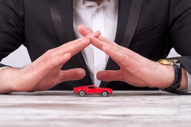 Mani dell'uomo d'affari del primo piano che proteggono un modello di automobile del giocattolo