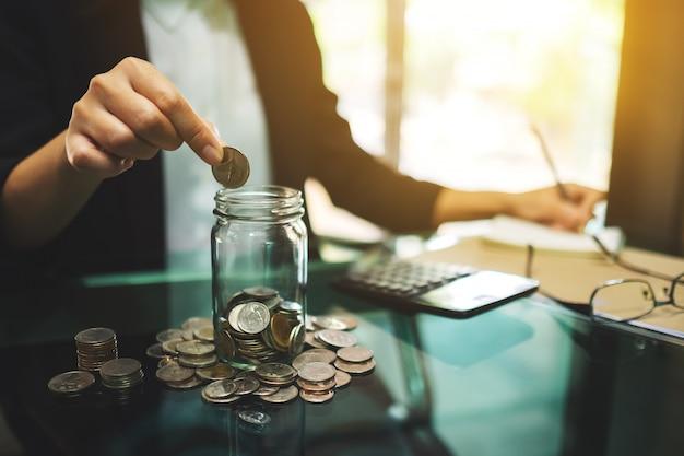Primo piano di una donna di affari che calcola, impilando e mettendo le monete in un barattolo di vetro per soldi di risparmio e concetto finanziario