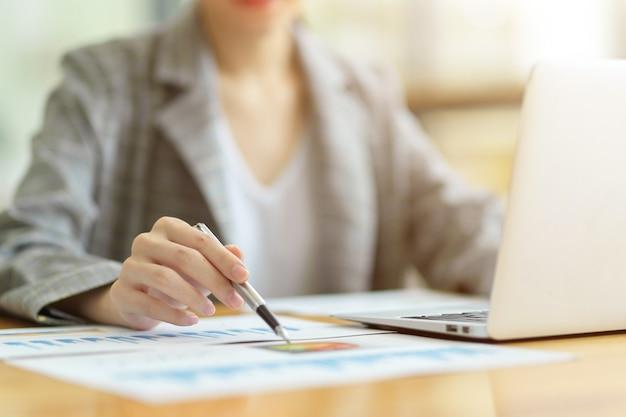 Primo piano della donna di affari o del ragioniere femminile che si siede e che lavora al computer portatile allo scrittorio. guardando il rapporto sui dati aziendali, puntando la penna su carta