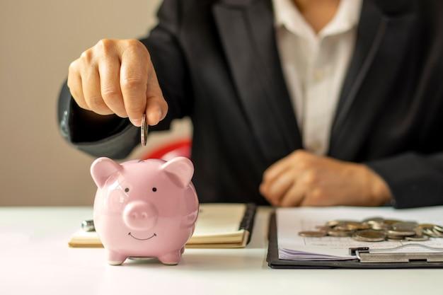 Primo piano di una donna d'affari che tiene una moneta in un salvadanaio, un concetto di risparmio di denaro per la contabilità finanziaria