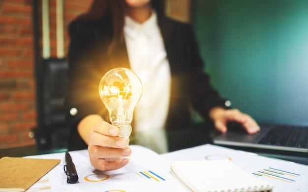 Primo piano di una donna di affari che tiene una lampadina d'ardore mentre lavorando al computer portatile in ufficio