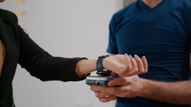 Primo piano della donna d'affari che effettua il pagamento senza contatto con l'orologio intelligente utilizzando il servizio terminale pos