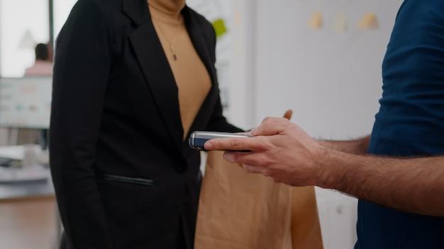 Primo piano della donna d'affari che paga l'ordine del cibo di consegna con carta di credito utilizzando contactless