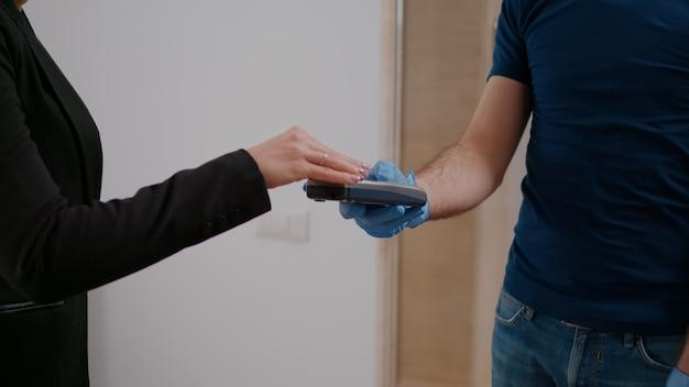 Primo piano della donna d'affari che paga con carta di credito ordine di cibo da asporto utilizzando il servizio senza contatto pos durante l'ora di pranzo