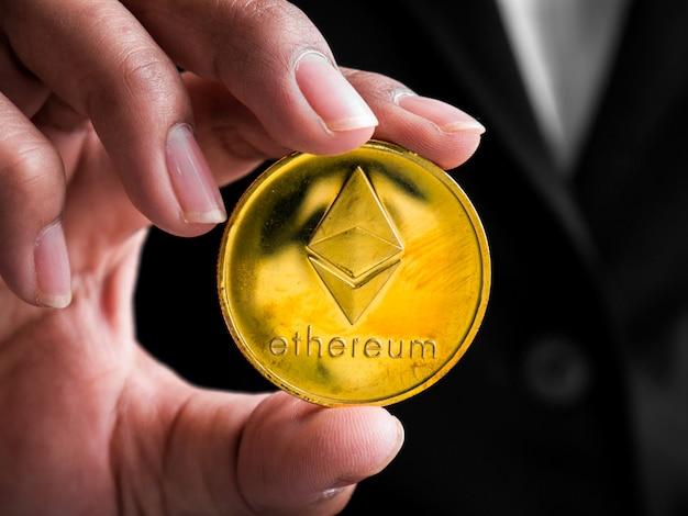 Donna di affari del primo piano che mostra la moneta di ethereum dell'oro.