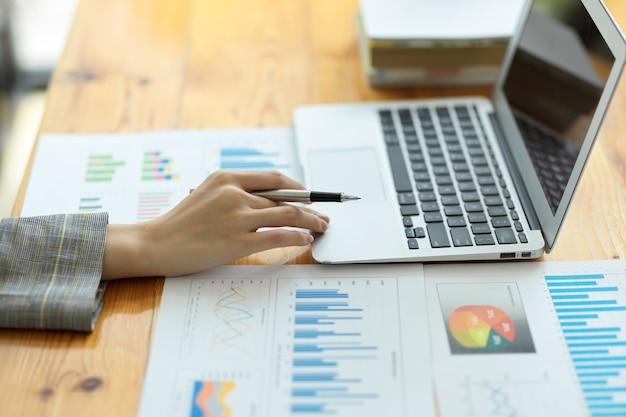 Primo piano imprenditrice che lavora al computer portatile alla scrivania controllando documenti grafici finanziari aziendali