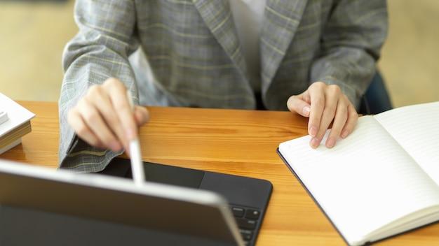 Primo piano imprenditrice che lavora su tablet portatile utilizzando la penna stilo sullo schermo