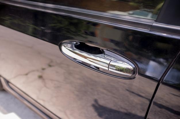 Primo piano della maniglia dell'automobile sulla porta di automobile nera chiusa con la riflessione