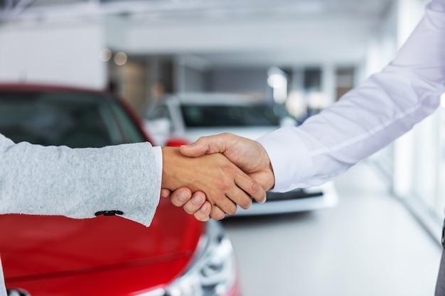Primo piano del venditore di auto e acquirente che agitano le mani mentre levandosi in piedi nel salone dell'automobile.