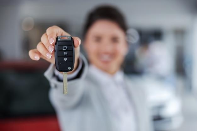 Primo piano del venditore di auto che tiene e consegna le chiavi di una macchina verso la telecamera mentre si sta in piedi nel salone dell'auto.