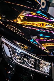 Primo piano dell'auto con luci al neon sulla strada notturna