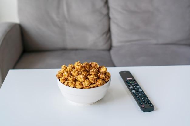 Primo piano di popcorn al caramello, telecomando per smart tv. guardare un film sul divano a casa concetto.