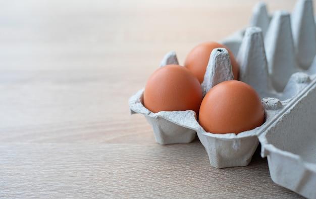 Primo piano sul cartone di tre uova ruspanti marroni fresche su una tavola di legno