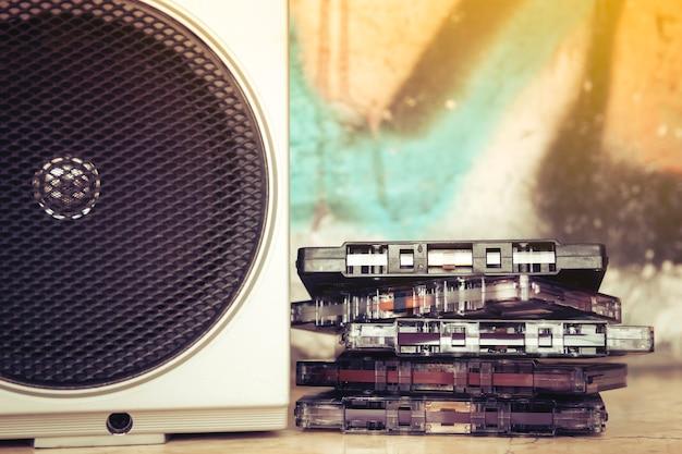 Primo piano delle cassette impilate accanto all'altoparlante di un vecchio stereo portatile