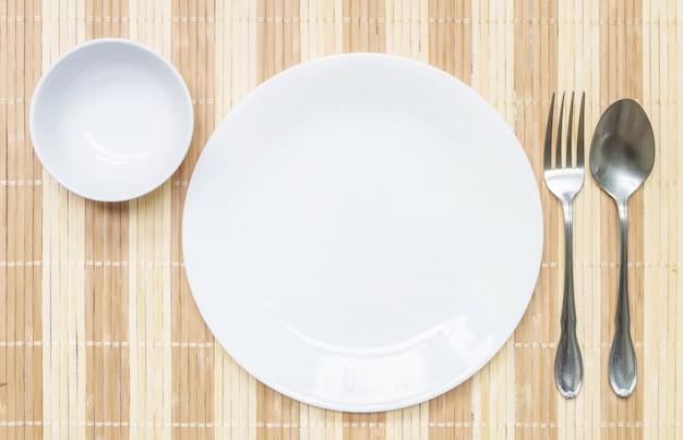 Piatto in ceramica del primo piano con la forchetta ed il cucchiaio dell'acciaio inossidabile sul fondo strutturato stuoia di legno