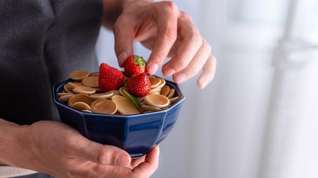 Primo piano frittelle di cereali nella ciotola blu con un pezzo di burro nelle mani degli uomini, concetto di cibo alla moda