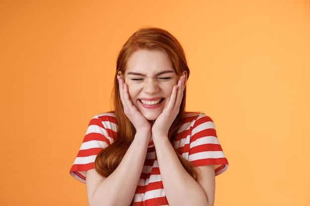 La ragazza sorridente eccitata fortunata allegra del primo piano non può credere che il tifo sente notizie eccellenti chiudi gli occhi c...