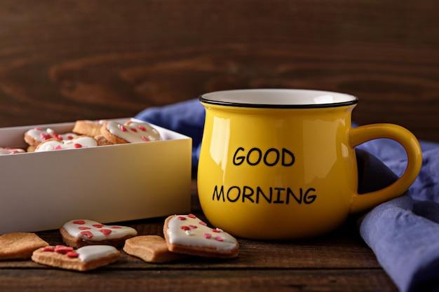 Mattina allegra del primo piano con la tazza di caffè o tè gialla con la scatola dei cuori dei biscotti su fondo di legno, concetto di buongiorno