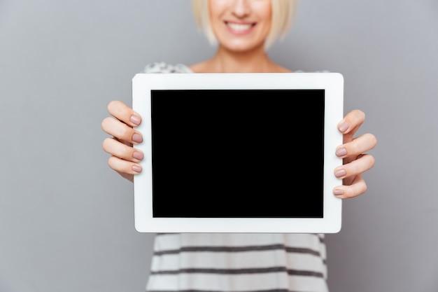 Primo piano della giovane donna allegra che tiene compressa dello schermo in bianco sopra la parete grigia