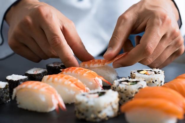 Primo piano delle mani di chef che preparano cibo giapponese
