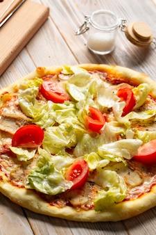 Primo piano sulla pizza caesar di pollo con pomodori e lattuga