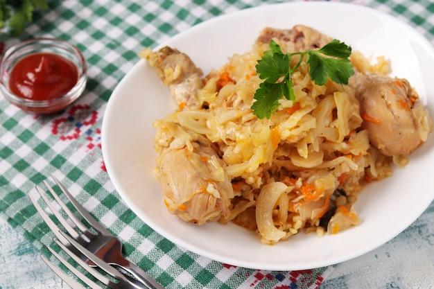 Primo piano delle cosce di pollo con riso e cavolo nel piatto bianco