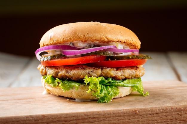 Primo piano su chickenburger con sottaceti sulla tavola di legno