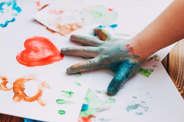 Primo piano del mosaico colorato dipinto a mano del bambino il bambino sta disegnando il palmo della mano su fogli con vernici